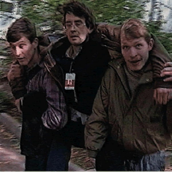 Rustem being carried on the backs of two strangers after being shot. (October 4, 1993)
