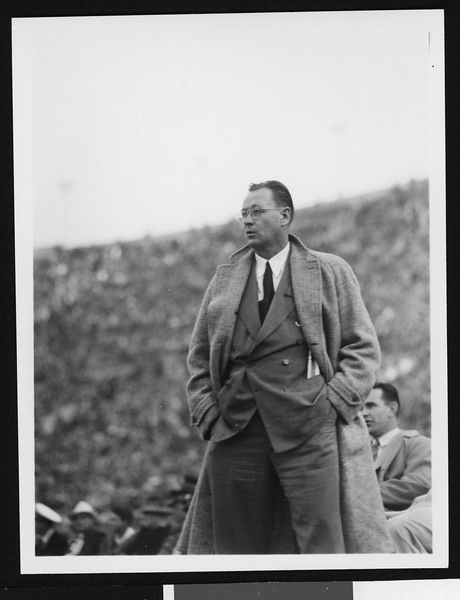 University of Southern California head football coach Jeff Cravath at the UCLA-USC game, hands in pockets, standing on sidelines, shot to knees, Los Angeles Coliseum, 1944.