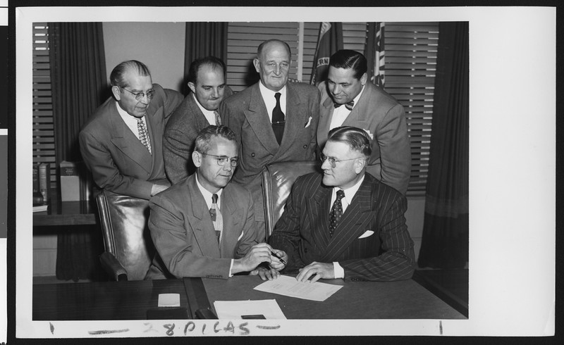 University of Southern California head football coach Jess Hill takes a pen from President Fagg as they sign Hill's new football contract, with Willett, Pappas, Hunter, and Bishop standing behind them, USC campus, January 1951.