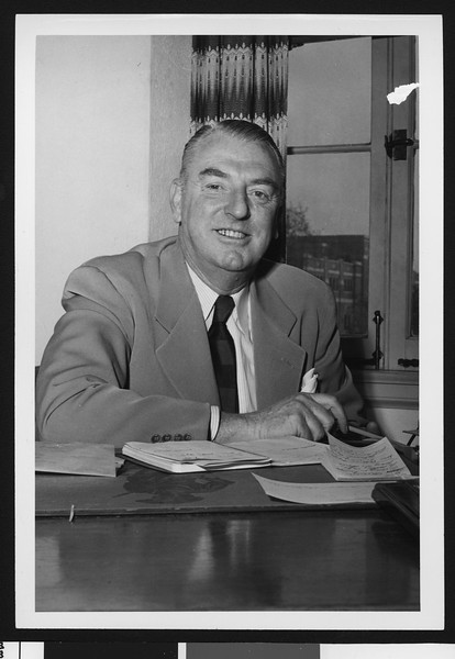 University of Southern California assistant football coach Sam Barry, in an office, wearing a suit and striped dark tie, USC campus, 1948.