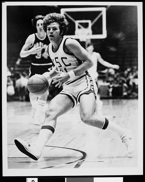 Mark Wulfemeyer, a USC guard, running forward with a basketball, 1975