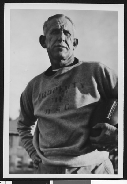 "University of Southern California football coach Howard Jones wearing ""Property of USC"" sweatshirt, holding football, Bovard Field, mid 1930s."