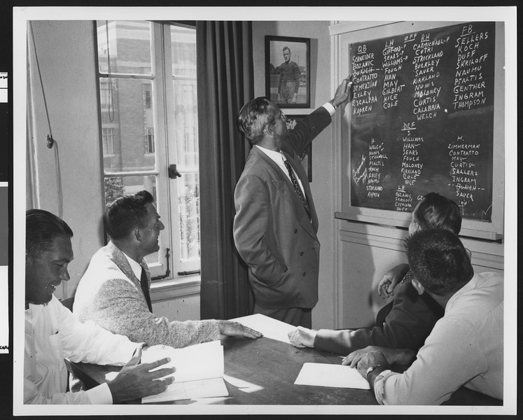 University of Southern California football coach Jess Hill pointing at a chalkboard with players' names on it, while four of his coaches look on, USC campus, 1951.