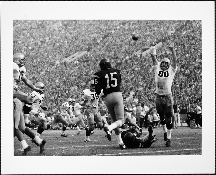 USC quarterback Craig Fertig passing to end Fred Hill in the game against Notre Dame, 1964