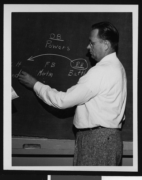 University of Southern California football coach Jeff Cravath diagramming a football play on a chalkboard, Los Angeles, 1949.