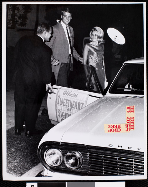 Two trojans in formal dress getting into a car, ca.1950