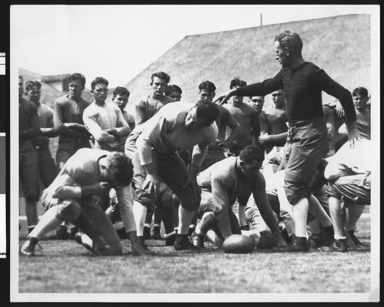 University of Southern California football coach Howard Jones in a coaching situation, pointing, players in formation. USC player John Wayne is in the background.
