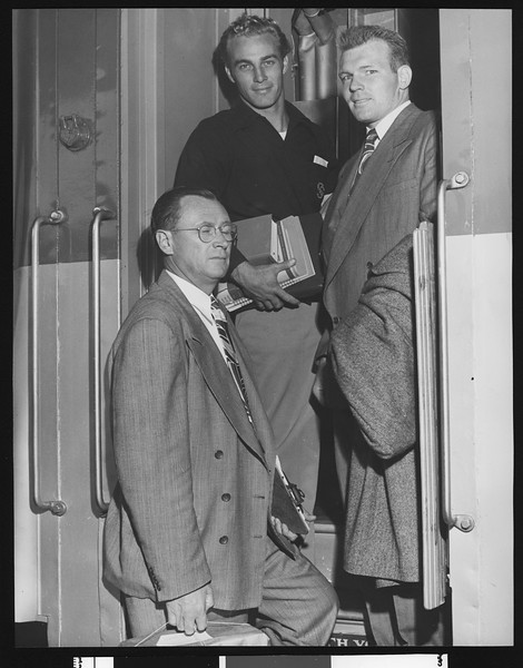 University of Southern California head football coach Jeff Cravath and USC players Dean Dill and Tony Linehan boarding a train, 1947.