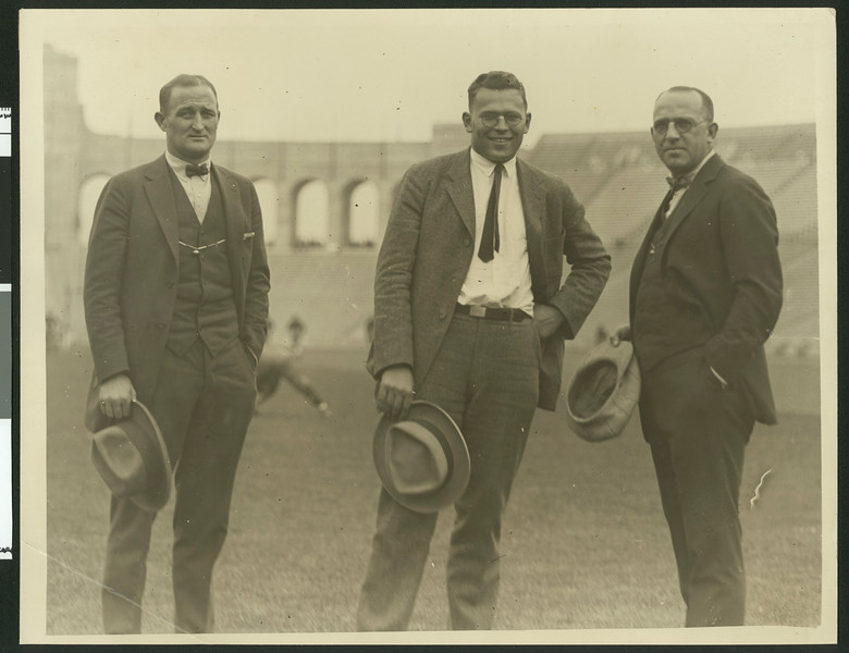 "University of Southern California football coaches Bill Hunter, John Thurman, and ""Gloomy Gus"" Henderson at Los Angeles Coliseum, ca. 1923."