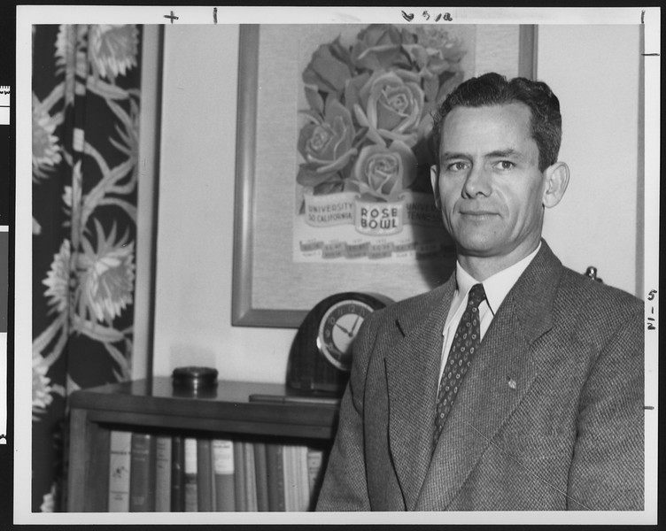University of Southern California head football coach Jess Hill in front of Rose Bowl poster in his office, USC campus, 1955.