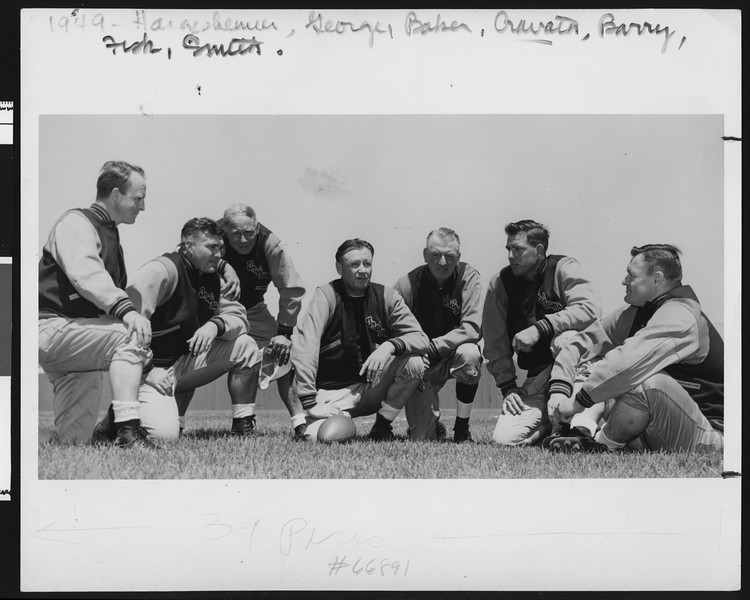 University of Southern California football coaching staff wearing letter jackets, 1949, Bovard Field, USC campus.