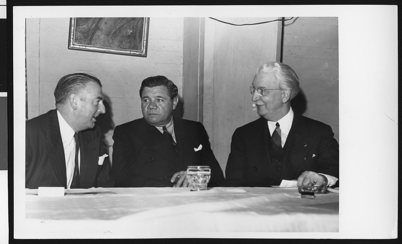 University of Southern California football coach Sam Barry, baseball player Babe Ruth, and USC President Rufus B. von KleinSmid at a dinner, location unknown, circa 1941.