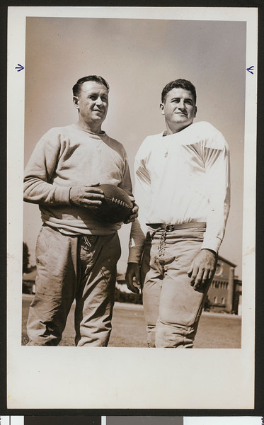 University of Southern California head football coach Jeff Cravath, holding football, with team captain Jim Callanan, Bovard Field. 1945.