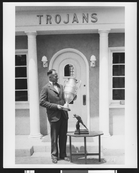 University of Southern California track & field coach Dean Cromwell with IC4A trophy in front of Trojan Hall, USC campus, Los Angeles, 1925.
