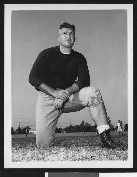 University of Southern California assistant football coach Ray George, wearing dark sweatshirt and posing on one knee, Bovard Field, 1949.