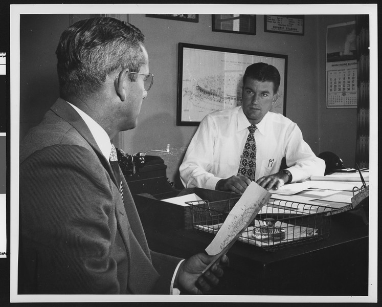 University of Southern California football coach Jess Hill talking to Assistant Athletic Director Alan Ewen in Ewen's office, August 1951.