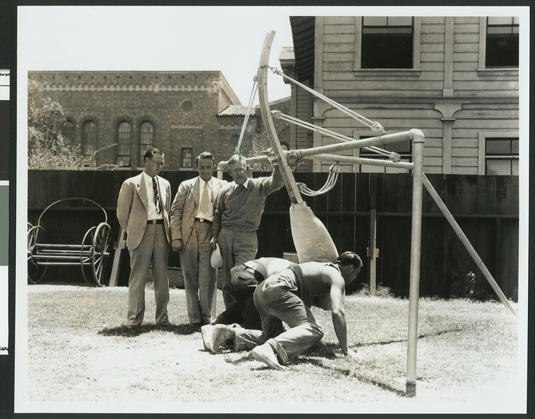 University of Southern California football coaches watch while two men try out a fixed position football training apparatus, Bovard Field, 1934.