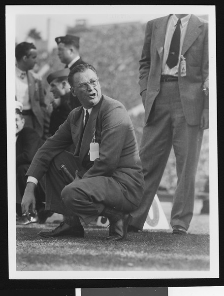 University of Southern California head football coach Jeff Cravath at the UCLA-USC game, crouching on the sidelines and yelling at someone while smoking, Los Angeles Coliseum, 1944.