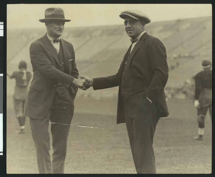 "University of Southern California athletic director Bill Hunter and head football coach ""Gloomy Gus"" Henderson shaking hands on the football field at Los Angeles Coliseum, 1923."