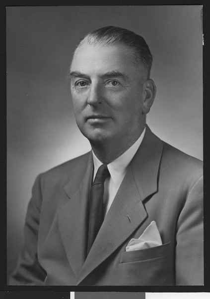 University of Southern California assistant football coach Sam Barry, posed in suit, solid tie, and handkerchief (not smiling), 1946.