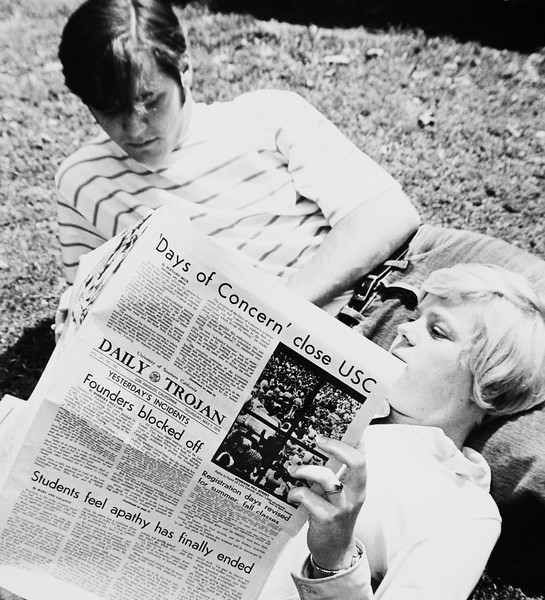 "Two students lying on the lawn with one reading the Daily Trojan with ""'Days of concern' close USC"" as the top headline, 1970"