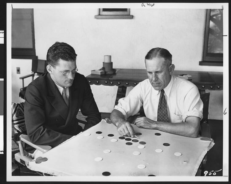 University of Southern California football coach Howard Jones uses poker chips to detail a play for John Baker, location unknown, 1933.