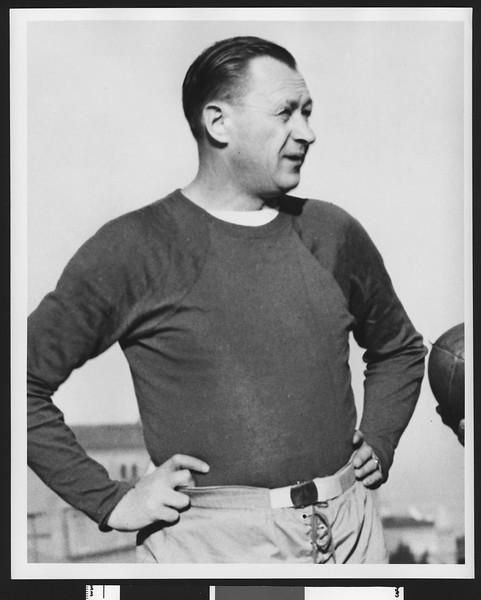 University of Southern California head football coach Jeff Cravath, hands on hips, wearing a dark sweatshirt. Bovard Field. 1947.
