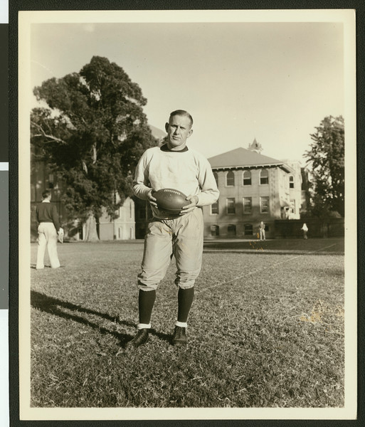 University of Southern California football coach Howard Jones, holding football on Bovard Field while standing, USC campus, 1933.
