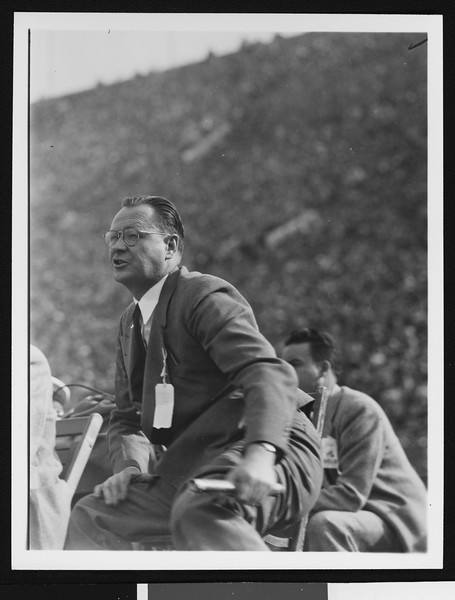 University of Southern California head football coach Jeff Cravath at the UCLA-USC game, sitting in a wooden chair on the sidelines yelling, Los Angeles Coliseum, 1944.