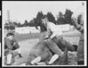 University of Southern California football coach Howard Jones in the middle of the action at football practice, coaching the varsity team. Bovard Field, mid-1930s.