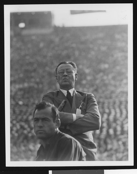 University of Southern California head football coach Jeff Cravath at the UCLA-USC game, arms crossed and lips pursed, Los Angeles Coliseum, 1944.