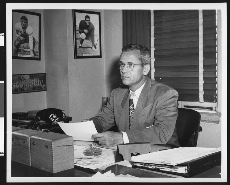 University of Southern California football coach Jess Hill sitting at his desk in his office, looking up to the ceiling, USC campus, 1951.