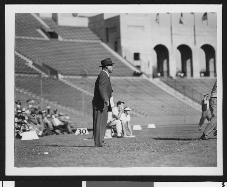 University of Southern California head football coach Jess Hill (right) yelling at a football pre-game practice at the Los Angeles Memorial Coliseum, with players and 10-yard markers behind him, 1951.