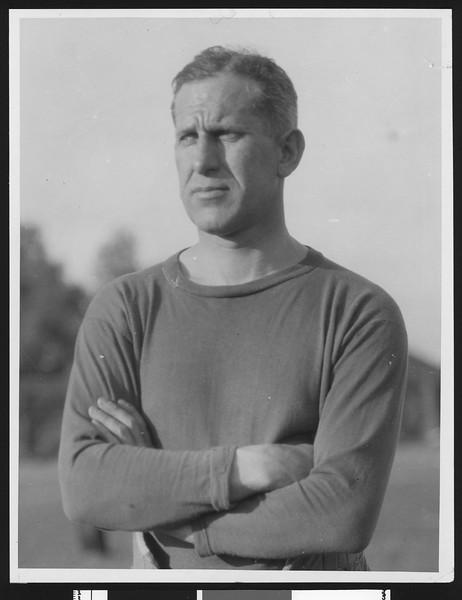 University of Southern California football coach Howard Jones, in darker sweatshirt with arms folded, torso up, mid 1920s.