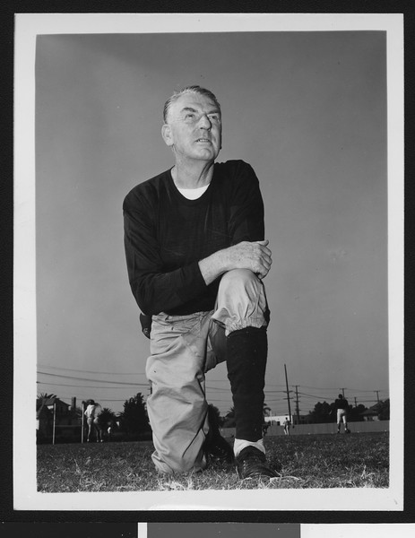 University of Southern California assistant football coach Sam Barry, on on knee, dark sweatshirt, Bovard Field, 1949.
