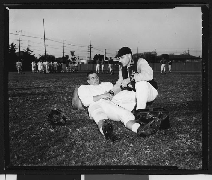 University of Southern California sports trainer Kearney Reeb examining the wrist of quarterback Jim Contratto, Bovard Field, 1951.