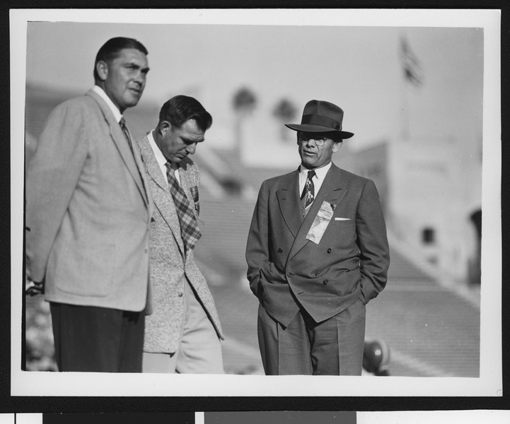 University of Southern California head football coach Jess Hill (right) talking to two other people at football pre-game practice at the Los Angeles Memorial Coliseum, 1951.