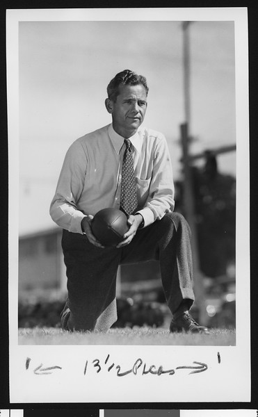 University of Southern California head football coach Jess Hill, on one knee, holding football, in tie and tweed pants, Bovard Field, 1951.
