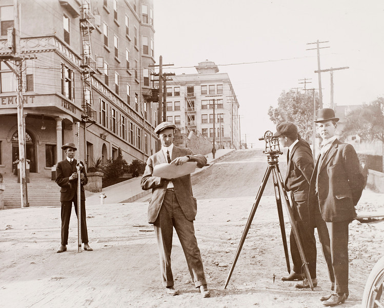 Three engineering students and a professor from USC surveying Fourth street in downtown Los Angeles, 1912
