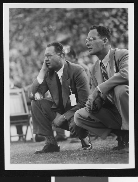 University of Southern California head football coach Jeff Cravath and coach Gus Shaver at the UCLA-USC game, crouching on the sidelines, Los Angeles Coliseum, 1944.