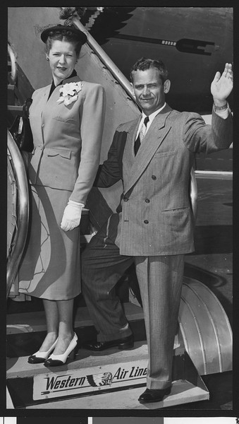 University of Southern California track coach Jess Hill waving as he boards a plane with his wife, Los Angeles Airport, 1948.