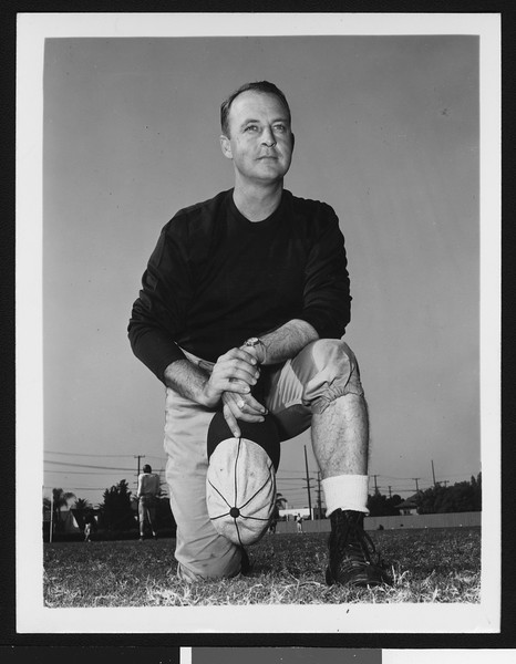 University of Southern California assistant football coach Walt Hargesheimer, dark sweatshirt, on one knee, holding cap in left hand, Bovard Field, 1949.