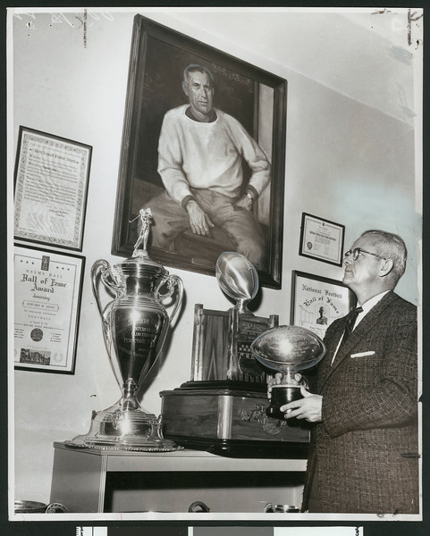 University of Southern California former football coach and athletic director Jess Hill looking up at portrait of Howard Jones and surrounded by football awards, USC campus, 1958.