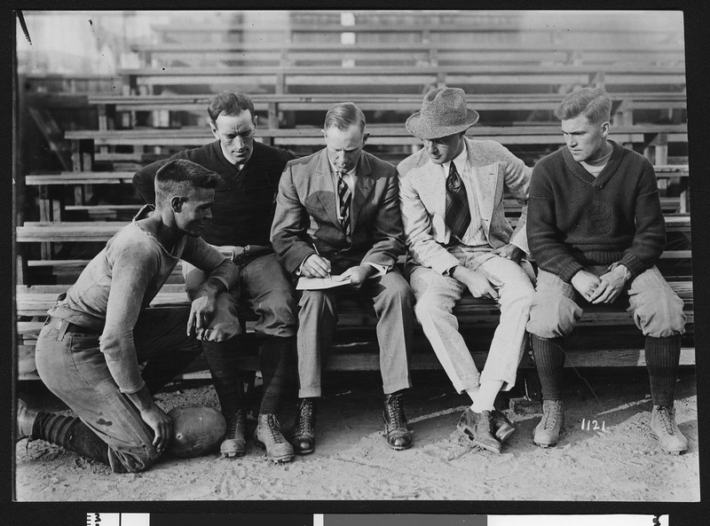 University of Southern California football coach Dean Cromwell with assistant coaches and players on bleacher seats, unknown location, 1916.
