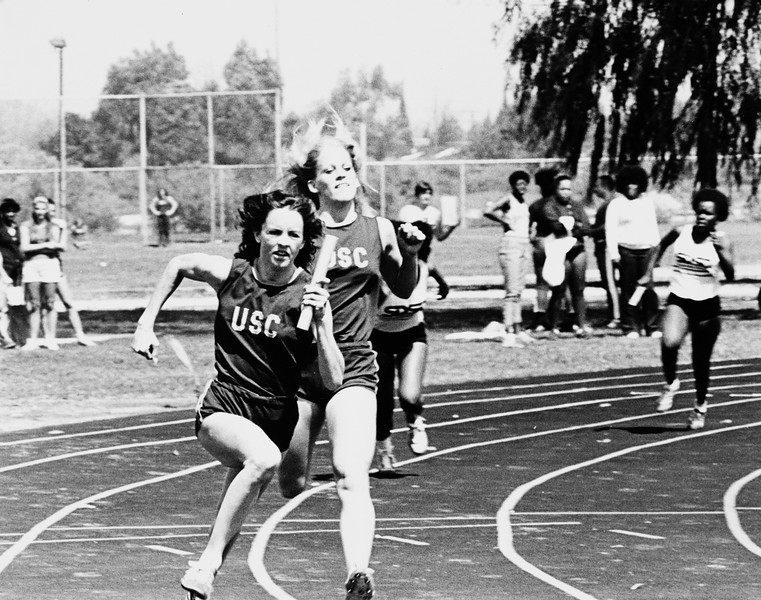 Lindsay Cassidy with baton and Sandy Crabtree of USC running in a relay race, 1979