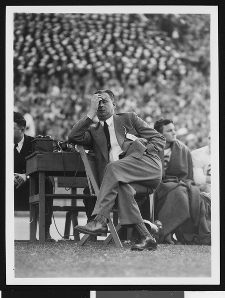 University of Southern California head football coach Jeff Cravath at the UCLA-USC game, sitting in a wooden chair on the sidelines rubbing his forehead, Los Angeles Coliseum, 1944.