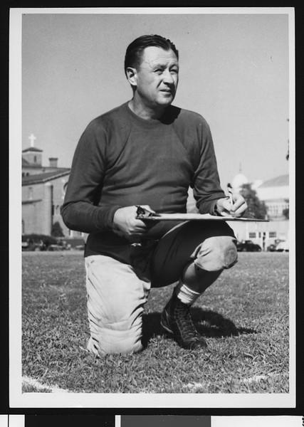 University of Southern California head football coach Jeff Cravath writing on clipboard, dark sweatshirt, standing on one knee, Bovard Field. 1947.