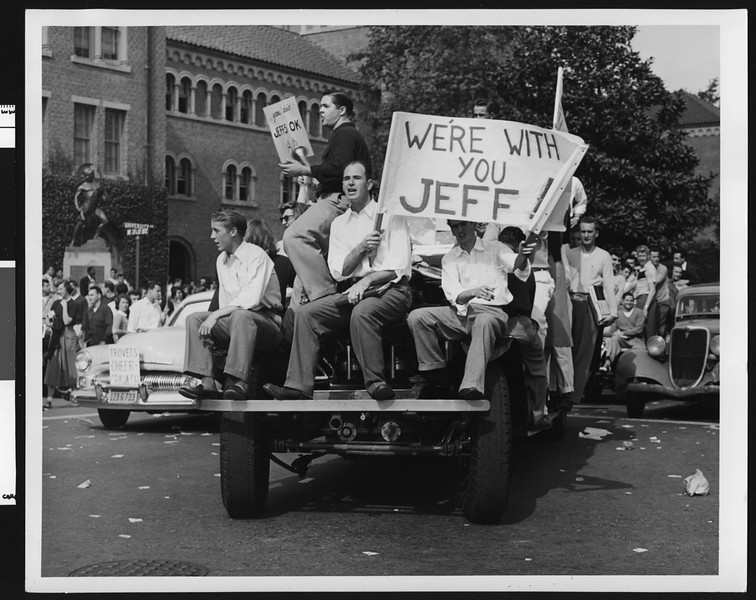 Student parade of cars and signs supporting University of Southern California football coach Jeff Cravath, USC campus, 1950.