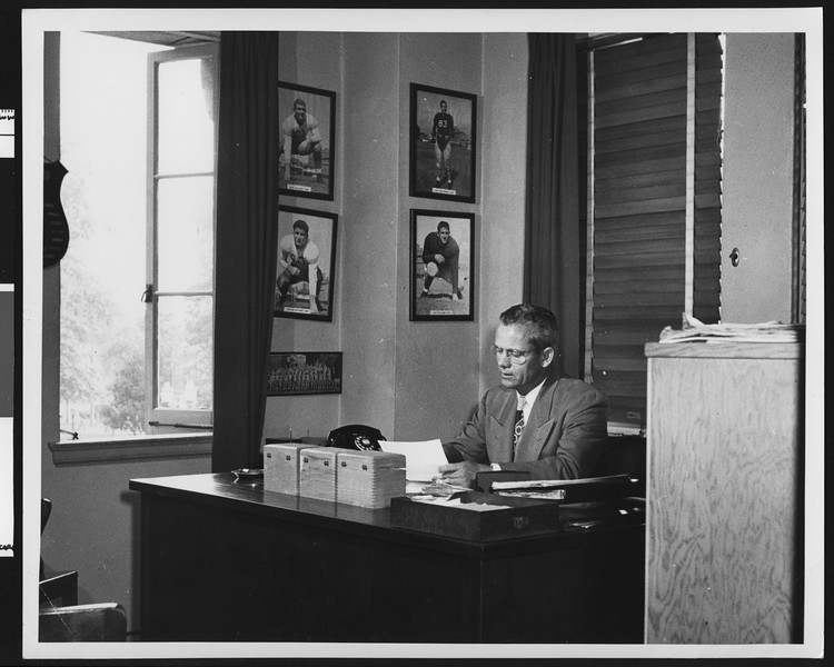 University of Southern California football coach Jess Hill sitting at his desk in his office, with the pictures of the great USC football players of the past hanging above him, USC campus, 1951.