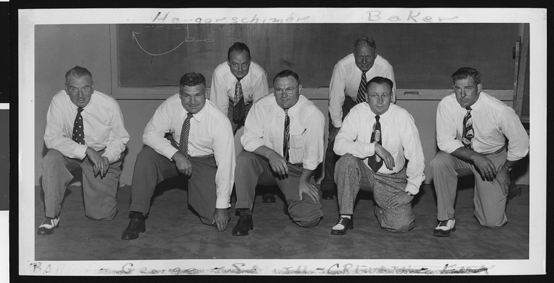 University of Southern California football coaching staff wearing white shirts and ties, 1949, USC campus classroom.